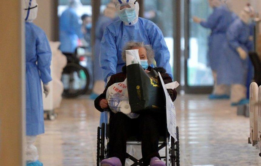 Enfermeiro transporta um paciente em hospital na China.